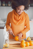 Mixed race woman using knife for cutting orange fruit for juice