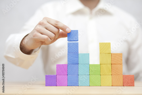 Man's hand stacking colorful wooden blocks. Business development concept - 181784849