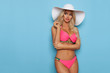 Sexy Blond Woman In Pink Swimsuit And White Sun Hat Is Looking Away