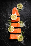 Fresh raw fish fillet cut into portions with lemon slices, salt and pepper on black stone background, top view - 181797006