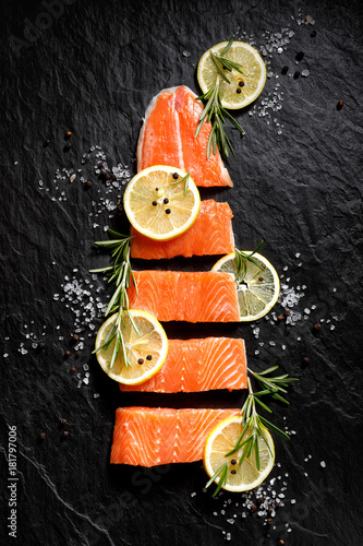 Poster Fresh raw fish fillet cut into portions with lemon slices, salt and pepper on bl