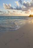 Peaceful morning at the beach. Shores of the Caribbean ocean during sunrise. Small foamy waves hitting the sandy beach. Vacation concept image, wallpaper. - 181810447