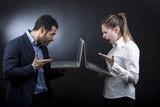 un uomo al computer scrive ad una ragazza che legge divertita (non si guardano anche se sono vicini) - sfondo scuro  - 181813639