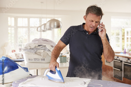 Poster Middle aged man distracted by phone while ironing