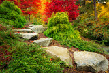 Stepping stones lead towards red japanese maple trees in Kubota Garden, Seattle Washington State. - 181862845