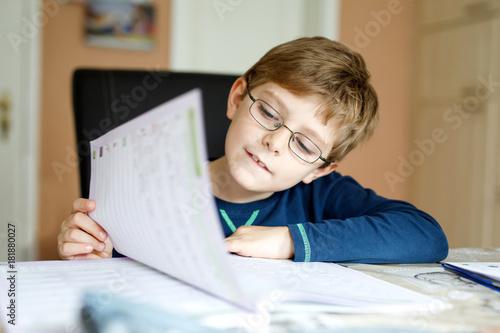 Fototapeta Happy school kid boy at home making homework