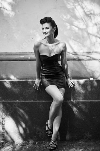 Poster Beautiful girl in a leather dress in rock and roll slyle, black and white photo