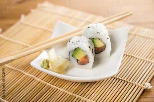 Fotobehang Sushi bar Zwei Inside Out Sushi mit Lachs und Avocado an Holz Stäbchen