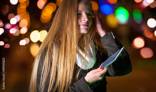 Beautiful woman using tablet in the city at night