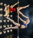 Two young sexy pole dance women