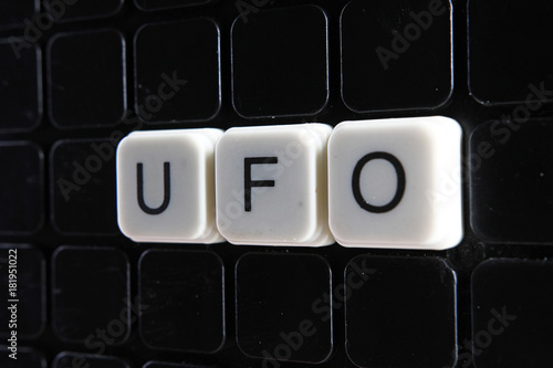 Fotobehang UFO UFO white text word on black cover. Text word crossword. Alphabet letter blocks game texture background texture.