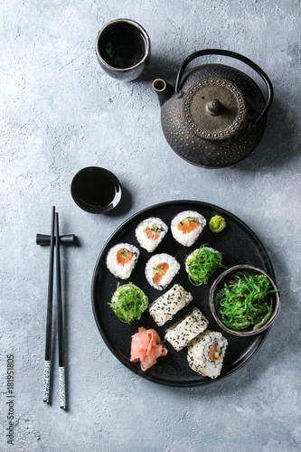 Fotobehang Sushi bar Homemade sushi rolls set with salmon, sesame seeds serving in black plate with pink pickled ginger, soy sauce, wasabi, seaweed salad, chopsticks on gray texture background. Top view, space