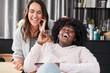 Zwei lachende Frauen hören Musik über Kopfhörer
