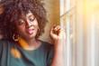 Junge Afrikanerin mit Makeup wartet an Fenster