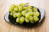 Bunch of ripe grape in black plate on wooden table