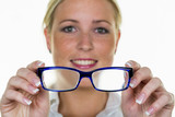 woman is holding a pair of glasses