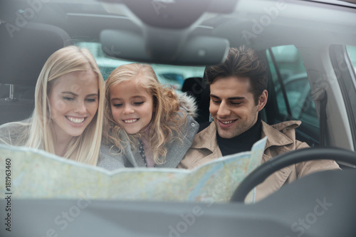 Sticker Happy young family in car holding map.
