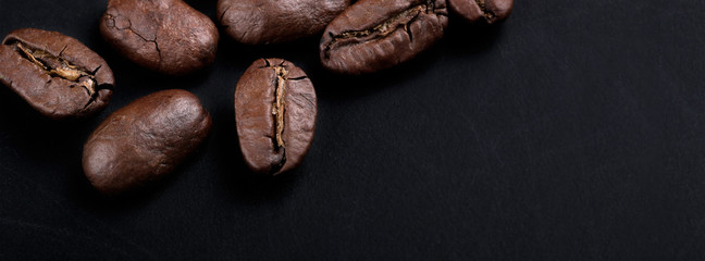 cover cracked grains of black fried coffee. slate background © lms_lms