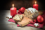 German Christmas cake, called criststollen with raisins and fruit, decoration from star cookies, red candles and balls on rustic wood, dark background - 181973648
