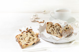 criststollen, typical german christmas cake with raisins and fruits, next to a cup of coffee, cinnamon stars and baubles on a white wooden background with copy space - 181974000