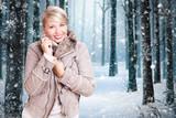 lächelnde junge Frau in Winterkleidung vor verschneiter Winterlandschaft