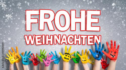 """viele angemalte Kinderhände mit Smileys vor Winter-Hintergrund mit """"Frohe Weihnachten"""" Nachricht"""
