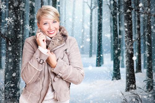 Plakát lächelnde junge Frau in Winterkleidung vor verschneiter Winterlandschaft