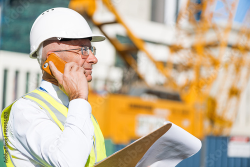 Fototapeta Man architector outdoor at construction area having mobile conversation