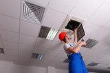 The worker inspects the wiring for ventilation - 181990219