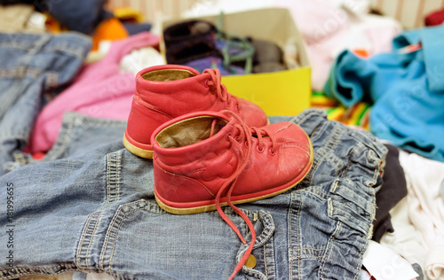 Leinwandbild Motiv Gebrauchte rote Schuhe für Kinder in einem Second Hand Laden