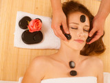 attractive young beautiful woman having facial massage with mineral stone - 182002673