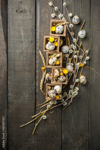 Poster Chicago Spring Easter basket with eggs of different sizes, spring flowers, cereals, willow branches. on a wooden dark background decorated with wheat and flowers. Place for text. Flat lay, top view