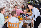 vigorous brunette waitress serving cheerful family in comfy family cafe - 182009048