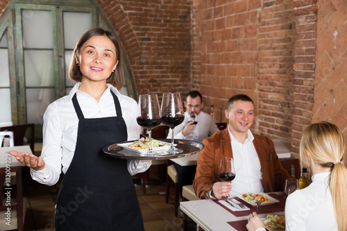 Smiling female waiter showing country restaurant