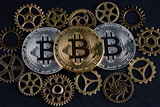 Three bitcoins among various cog wheels. Cryptocurrency concept. - 182009668