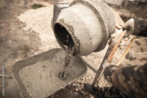 Fototapeta worker pours concrete mortar on a construction site