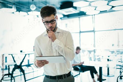 Confident businessman using tablet