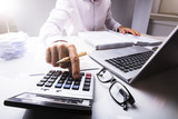 Businessman Calculating Tax Using Calculator - 182023869