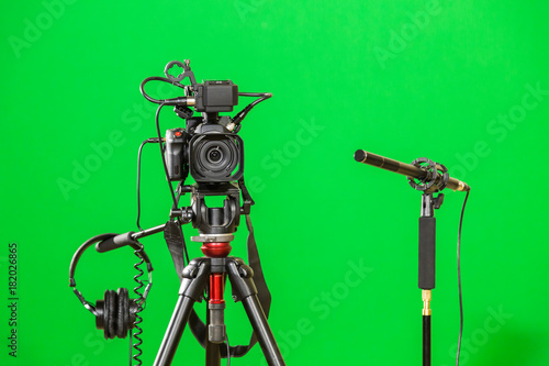 Video camera on a tripod, headphones and a directional microphone on a green background. The chroma key. Green screen. - 182026865