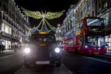 Red double-decker bus and black cabpass under twinkling Christmas lights along the upscale shopping district of Regent Street. - 182032887