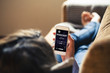 Woman at home holding a mobile phone with podcast app in the screen while lies down on the sofa.