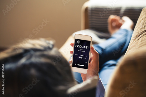 Woman at home holding a mobile phone with podcast app in the screen while lies down on the sofa. - 182033486