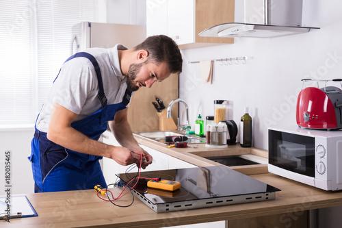 Tuinposter Hoogte schaal Technician Repairing Induction Stove In Kitchen
