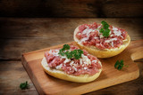german mettwurst brotzeit, minced pork sausage with onions and parsley garnish on buns, cutting board on a dark rustic wooden background, copy space - 182045693
