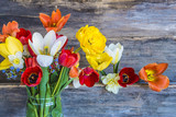 bouquet of fresh multicolored tulips on rustic background