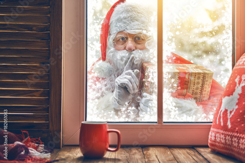 Santa Claus is knocking at window - 182051063