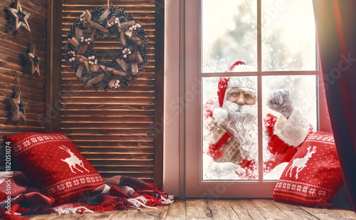 Santa Claus is knocking at window - 182051074