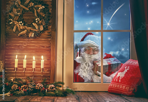 Santa Claus is knocking at window - 182051095