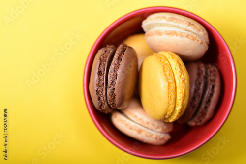 Foto op Aluminium Macarons Lemon, vanilla and chocolate french macarons in the red bowl on the yellow background.