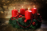 Advent wreath with four red burning candles and christmas decoration on rustic dark wood - 182080697